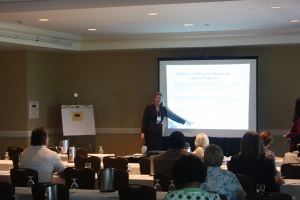 Presenter at white screen giving a presentation