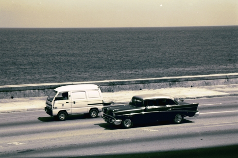 2 Cars driving along the sea wall