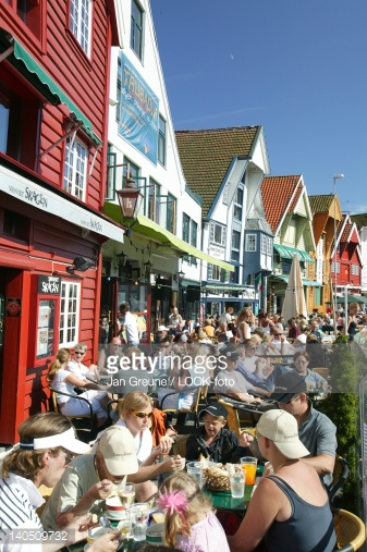 People dining outside of a restaurant in Norway on a sunny day.