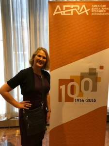 Sandra Rogers standing near AERA conference sign celebrating 100 years