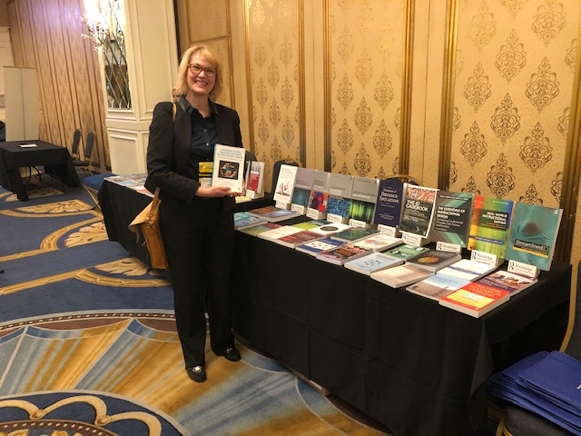 Sandra Rogers is holding the educational book in which she is a co-author. She's standing in front of a table of other books displayed by Routledge.