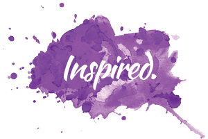The word, Inspired, is written against a purple splash of paint.